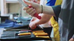 Un gruppo di cuochi unici affila i coltelli I fornelli prepara per la classe matrice stock footage