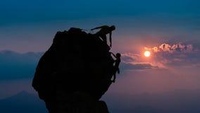 Un gruppo di due alpinisti roped dentro per aiutarvi a conquistare il picco Fotografia Stock