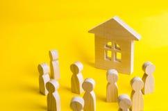 Un gruppo di figure di legno della gente circonda ed esamina la casa di legno Giovani alla ricerca di alloggio accessibile Presti Fotografie Stock