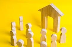 Un gruppo di figure di legno della gente circonda ed esamina la casa di legno Giovani alla ricerca di alloggio accessibile Presti Fotografie Stock Libere da Diritti