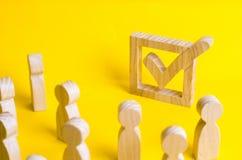 Un gruppo di figure di legno della gente circonda ed esamina un segno di spunta nella scatola Gli elettori partecipano alle elezi Fotografie Stock
