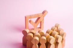 Un gruppo di figure di legno della gente circonda ed esamina un segno di spunta nella scatola Gli elettori partecipano alle elezi Fotografia Stock