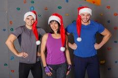 Un gruppo di gente di sport in cappelli di Santa che stanno felicemente e che sorridono Contro la parete per scalare Fotografia Stock Libera da Diritti