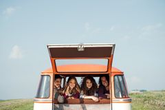 Un gruppo di giovani amici su un roadtrip attraverso la campagna, guardante dalla finestra immagine stock