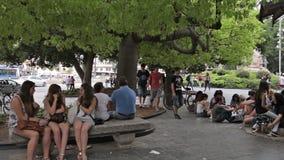 Un gruppo di giovani che hanno un resto in un parco della città stock footage