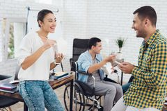 Un gruppo di giovani e l'uomo in sedia a rotelle sono parlanti e mangianti l'alimento tailandese Sono in un ufficio luminoso Fotografia Stock