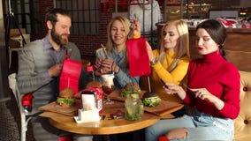 Un gruppo di giovani nel ristorante, ottengono gli hamburger saporiti pronti da mangiare stock footage