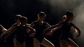 Un gruppo di giovani ragazze della ballerina che ballano in scena nello scuro, primo piano archivi video