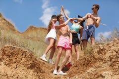 Un gruppo di giovani sorridenti si dà a cinque su una cima di una valle su un fondo vago naturale Fotografia Stock