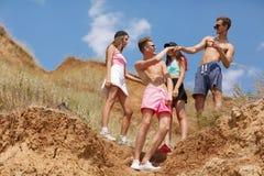 Un gruppo di giovani sorridenti si dà a cinque su una cima di una valle su un fondo vago naturale Immagini Stock