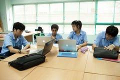 Un gruppo di giovani studenti fa il loro compito in un'aula Fotografia Stock
