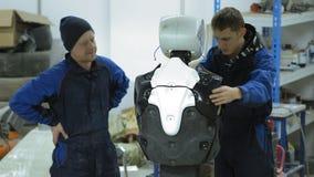 Un gruppo di ingegneri crea un robot o un androide moderno Elementi rotti di riparazione e del controllo Fabbrichi e fabbrichi di fotografie stock libere da diritti