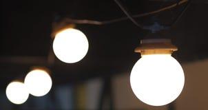 Un gruppo di 4 lampadine in una linea su un fondo scuro immagine stock libera da diritti