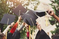 Un gruppo di laureati che gettano i cappucci di graduazione nell'aria Fotografie Stock Libere da Diritti