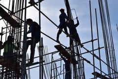 Un gruppo di lavoratori dell'industria siderurgica della costruzione filippina che montano le barre d'acciaio su grattacielo senz Immagini Stock
