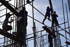 Un gruppo di lavoratori dell'industria siderurgica della costruzione filippina che montano le barre d'acciaio su grattacielo senz Fotografie Stock