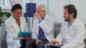 Un gruppo di medici di tre medici si siede sullo strato all'ospedale archivi video
