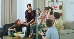 Un gruppo di multi amici etnici molto carismatici si diverte insieme sul sof? in salone essi la birra bevente stock footage