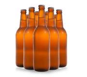 Un gruppo di nove bottiglie di birra in una formazione di diamante sul BAC bianco Fotografia Stock