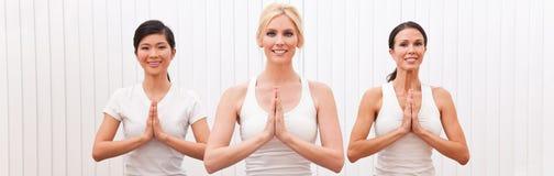Un gruppo di panorama di tre belle donne nella posizione di yoga immagine stock