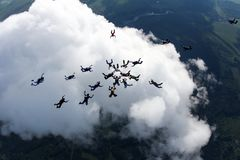 Un gruppo di paracadutisti sopra la grande nuvola bianca fotografia stock libera da diritti
