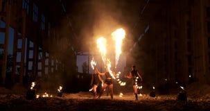 Un gruppo di persone con fuoco e le torce che ballano al tramonto nel capannone al rallentatore Inforni l'esposizione video d archivio