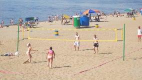 Un gruppo di persone, gli uomini e le donne giocanti beach volley archivi video