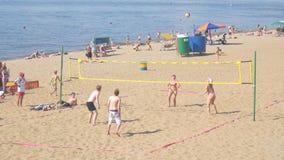 Un gruppo di persone, gli uomini e le donne giocanti beach volley stock footage