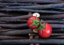 Un gruppo di pomodori su un fondo di vimini con i gambi In uno stile rustico Piccoli pomodori di ciliegia rossi fotografia stock