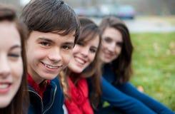 Un gruppo di quattro adolescenti felici all'esterno Immagine Stock
