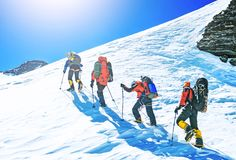 Un gruppo di quattro alpinisti che scalano una montagna Fotografie Stock Libere da Diritti