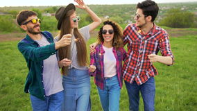 Un gruppo di quattro amici sorridenti felici cammina con le stelle filante a movimento lento archivi video