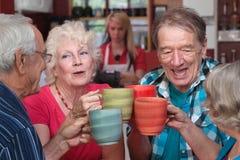 Un gruppo di quattro anziani che celebrano Immagine Stock