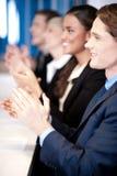 Un gruppo di quattro corporates che applaude Immagini Stock