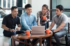 Un gruppo di quattro ha dedicato gli impiegati che lavorano insieme ad un progetto innovatore immagine stock libera da diritti