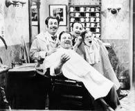 Un gruppo di quattro uomini ad un canto del negozio di barbiere (tutte le persone rappresentate non sono vivente più lungo e ness fotografia stock libera da diritti