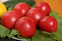 Un gruppo di sei pomodori maturi rossi con le gocce di acqua si trova sulle foglie di una lattuga Fotografie Stock