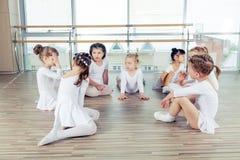 Un gruppo di sette piccole ballerine che si siedono sul pavimento Sono Immagine Stock Libera da Diritti