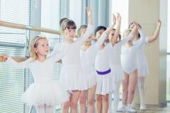 Un gruppo di sette piccole ballerine che stanno nella fila e nel balletto di pratica facendo uso del bastone sulla parete Fotografie Stock Libere da Diritti