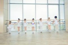 Un gruppo di sette piccole ballerine che stanno nella fila e nel balletto di pratica facendo uso del bastone sulla parete Immagini Stock