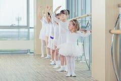 Un gruppo di sette piccole ballerine che stanno nella fila e nella pratica Fotografia Stock
