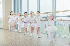 Un gruppo di sette piccole ballerine che stanno nella fila e nella pratica Fotografie Stock Libere da Diritti