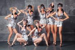 Un gruppo di sette ragazze sveglie felici in costume da discoteca d'argento Fotografia Stock