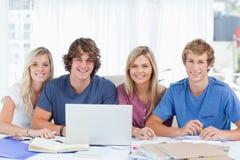 Un gruppo di studenti con uno sguardo del computer portatile nella macchina fotografica Fotografie Stock Libere da Diritti