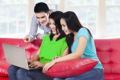Un gruppo di studio che lavora al computer portatile Immagini Stock