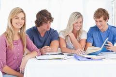 Un gruppo di studio che lavora duro come una ragazza sorride Fotografia Stock