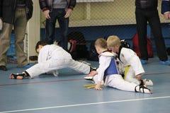 Un gruppo di taekwondo che si siede sul pavimento per un resto fotografia stock libera da diritti