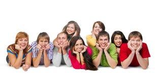 Un gruppo di tipi e di ragazze che si trovano sul pavimento Fotografia Stock Libera da Diritti