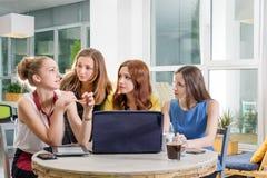 Un gruppo di togeather di lavoro della donna di affari graziosa quattro con il nuovo progetto startup facendo uso del computer po Fotografie Stock