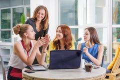 Un gruppo di togeather di lavoro della donna di affari graziosa quattro con il nuovo progetto startup facendo uso del computer po Fotografie Stock Libere da Diritti